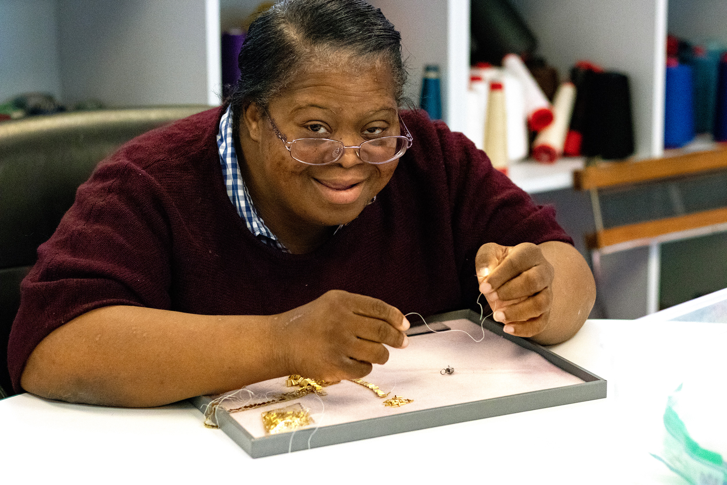 Adult program participant working on jewelry piece