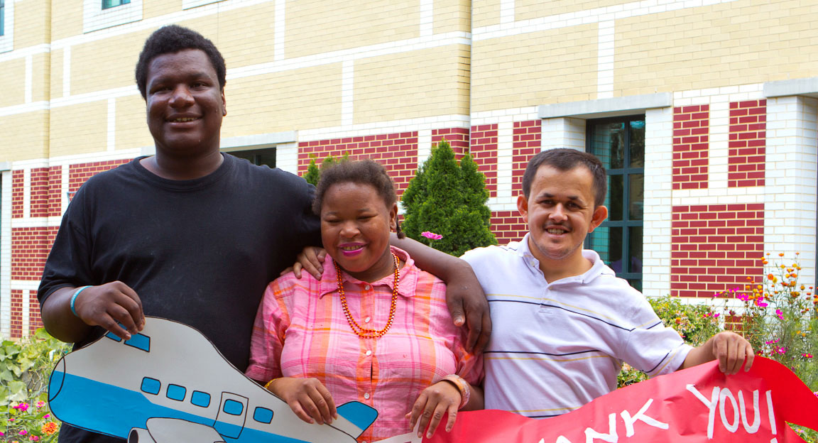 three students holding artwork